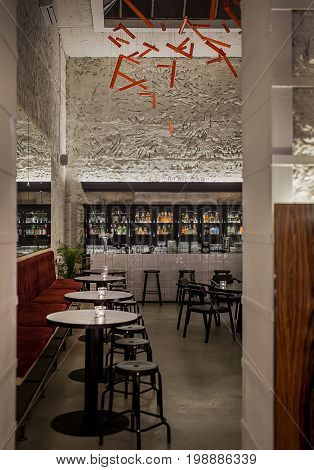 Glowing bar with textured walls and a large window on the ceiling. There are red sofas, black round tables, dark stools and chairs, plants, tiled bar rack, shelves with bottles, hanging red lamps.