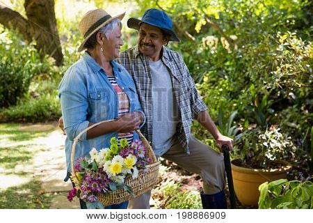 Senior couple walking in garden with flower basket