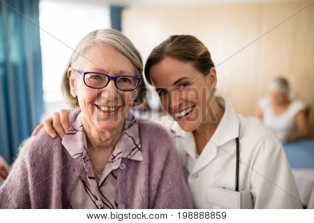 Portrait of smiling female doctor standing arm around senior woman at retirement home