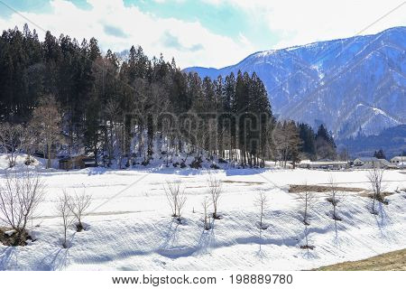 Hakuba mountain range in the winter with snow on the mountain and blue sky and clouds background in Hakuba Nagano Japan.