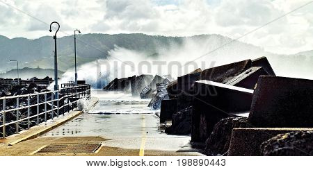 Huge seven meter seas breaking over the Coffs Harbour Marina breakwall during a savage winter sea storm. Photographed at Coffs Harbour New South Wales Australia.