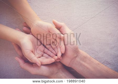 adult holding child hands copy space background pray health hope support concept