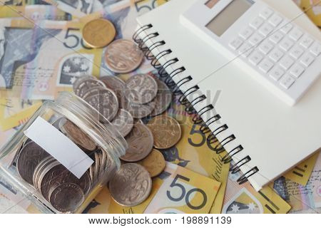 Australian Money In Glass Jar, Aud With Calculator, Notebook, Saving Concept