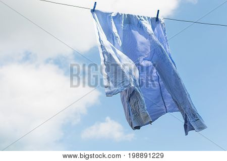 White shirt hanging to dry on clothes line