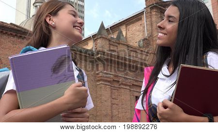Two Female Teen Students and Holding Textbooks