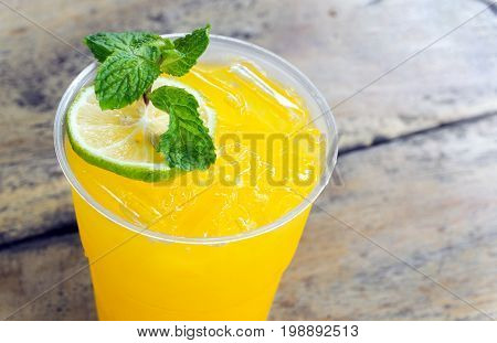 Closeup glass of Orange and Lemon soda drink on wood table background selective focus