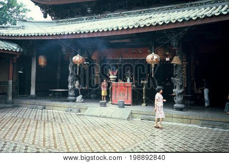 SINGAPORE / CIRCA 1990: Worshipers light candles, burn joss sticks, kneel and pray before sacred images in the Kwan Im Thong Hood Cho Temple.