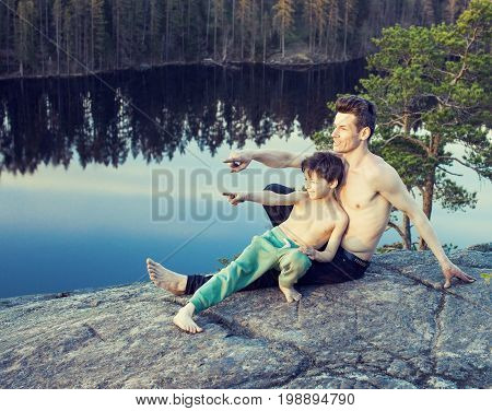middle age man with little cute son doing sport yoga on the top of the mountain together, happy family lifestyle people outdoor, summer wild nature for training close up