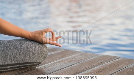 Closeup woman yoga finger acting on hands in soft focus background with nature surrounding. Concept of healthy lifestyle and relaxation.