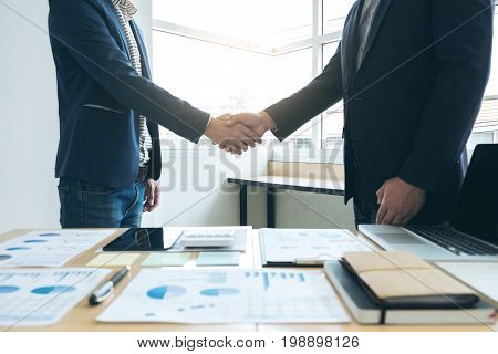 Two business men shaking hands during a meeting to sign agreement and become a business partner companies confident success dealing contract between their firms