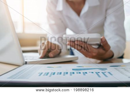 Female accountant calculations and analyzing financial graph data with calculator and laptop Business Financing Accounting Doing finance Economy Savings Banking Concept.