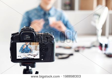 Happy smiling elegant woman or beauty blogger with brush on recording video while review product make up tutorial for theme about video blogging on camera screen.