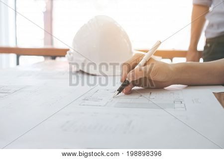 Image of engineer or architectural project Close up of Architects engineer's hand drawing plan on BluePrint with Engineering tools on workplace Construction concept.