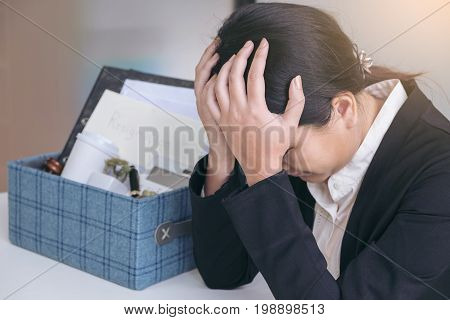 Images of packing up all her personal belongings and files into a brown cardboard box and Business woman has stress to resignation in modern office resign concept.
