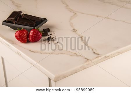 Marble. Kitchen counter top made of marble. White carrara marble of kitchen counter top with strawberries and chocolate decoration. White marble counter top concept.