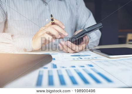 Business man or accountant working Financial investment on calculator with calculate Analyze business and market growth on financial document data graph and tablet Accounting Economic commercial.