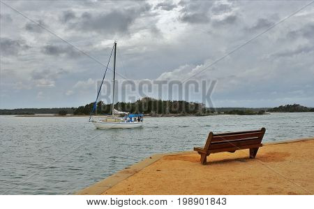 Sailboat on the water with dark cloudy skys