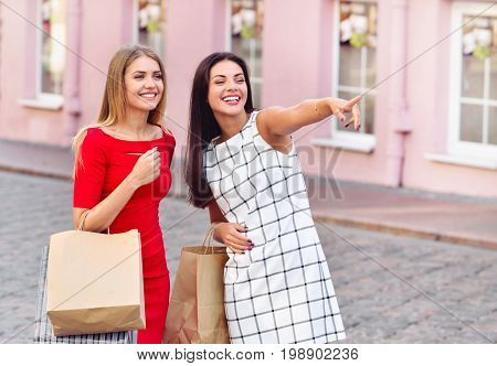 Happy Young Women With Shopping Bags Pointing Finger Somewhere