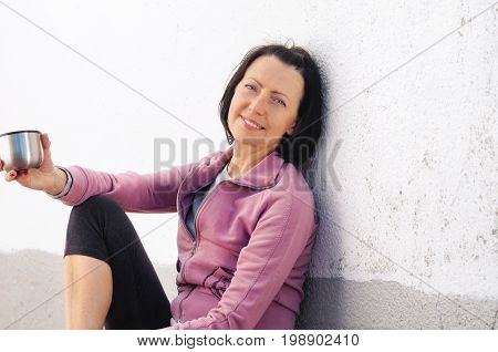 Portrait Of Mature Woman Resting After Jog Near The Wall With Cup In Hand