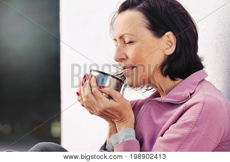 Portrait Of Mature Woman Resting After Jog In The Park With Cup Of Hot Tea