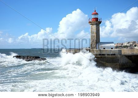 Storm waves over lighthouse and blue sky in Porto, Portugal