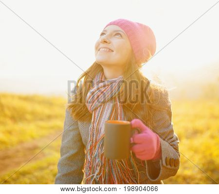 Young Smiling Woman With Mug In Hand Looking At The Autumn Sky