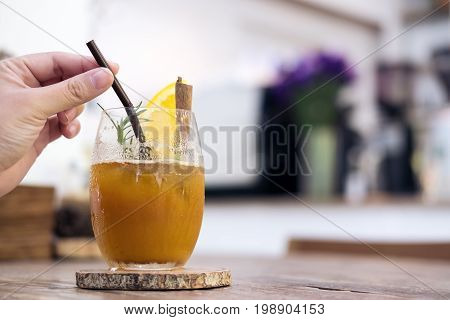 Closeup image of a woman's hand picking straw in a glass of orange cold brew coffee on wooden table in cafe