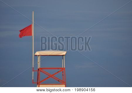 Tower of a marine lifeguard with a red flag hanging out. Swimming prohibited.