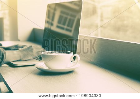 Young man using laptop with wifi connection and drink coffee at restuarant bar.