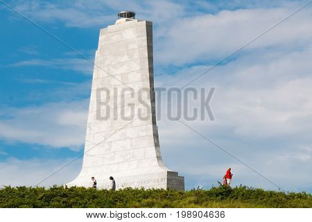 KILL DEVIL HILLS, NORTH CAROLINA - JULY 14, 2017:  People visit the granite tower designed by Rodgers and Poor, a New York City architectural firm, at the Wright Brothers National Memorial.