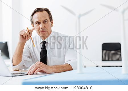 In search of ides. Pleasant senior man sitting in the office in front of a laptop and looking at the wind turbine models