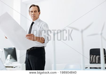 Busy day. Handsome serious man staying in the middle of the office, holding a big blueprint while looking at the wind turbine models