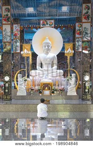Khon Kaen Thailand - August 02 2017 : Asian Buddhist woman wearing white dress sitting and paying respect to big white Buddha statue in Wat Pa Thamma Utthayan public Buddhism temple in Khon Kaen Thailand