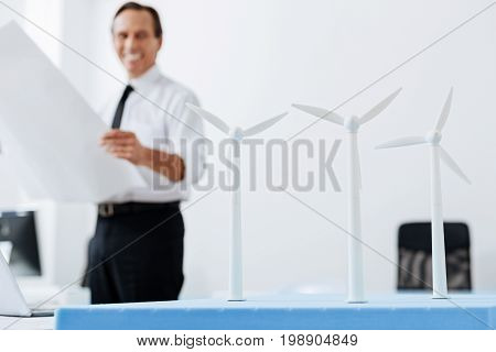 Great results. The focus being on three wind turbine models staying on the table while the smiling man holding a blueprint and looking at them with a broad smile