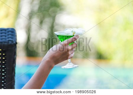 Woman in swimsuit relaxing with cocktail on chaise-longue