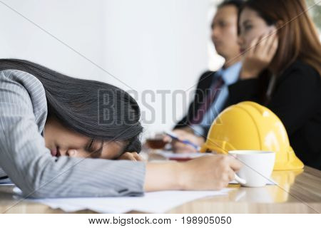 Bored businesswoman taking a nap in conference meeting room