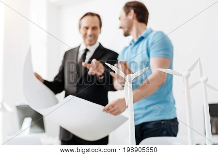 Fruitful collaboration. Two gifted engineers holding a big blueprint of a wind power station and discussing its details while the man in a suit pointing at the wind turbine models being in a focus