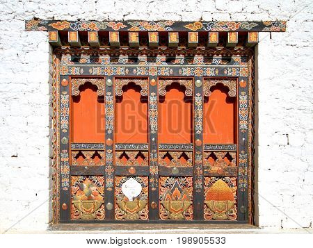Traditional Bhutanese style building decorated with carved wood window frames in Paro Rinpung Dzong Buddhist monastery and fortress on a hill near the Paro Chu river. Paro Bhutan.