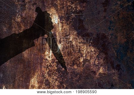 Human hand with killing kitchen knife silhouette in shadow on rust wall background. Illustration for criminal chronicles.