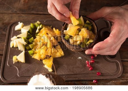 Close up process of preparing and decoration of tropical fruit salad in coconut shell. Orange, apple, kiwifruit and pomegranate ingredients are mixed in nut bowl