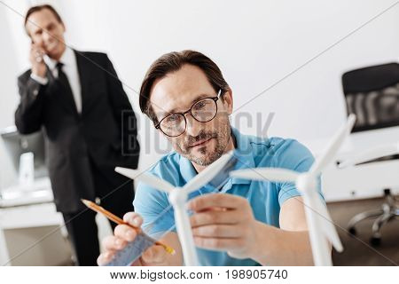 Thorough work. Pleasant young man sitting at the table and measuring a sail of a wind turbine model with the help of a ruler while his boss discussing work on the phone in the background