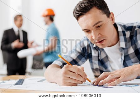 Working thoroughly. Charming young man sitting at the table and tracing a line with the help of a ruler and a pencil while his colleagues discussing work in the background
