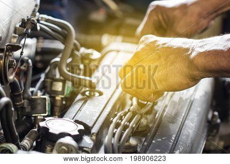 Close up mechanical man dirty hands using tool to fix repair car engine maintenance vehicle service concept.