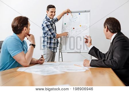Important remarks. Pleasant cheerful young architect standing near the whiteboard and pointing at the printout on it with a pencil while his colleagues listening to him and making their comments