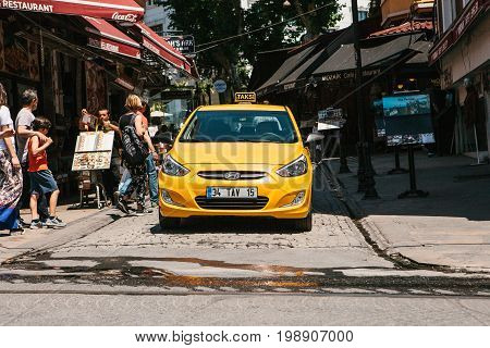 Editorial image of yellow taxi cab in shopping district in Istanbul, Turkey on June 16, 2017.
