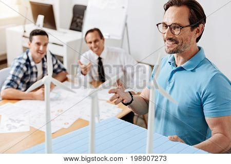 Work brings pleasure. Handsome young man showing a wind power station model to his colleagues and looking pleased by his work while the colleagues reacting emotionally to it