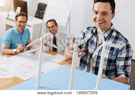 Inspired speaker. Attractive young man holding a wind power station model and speaking enthusiastically about it while his upbeat colleagues listening to him with smiles