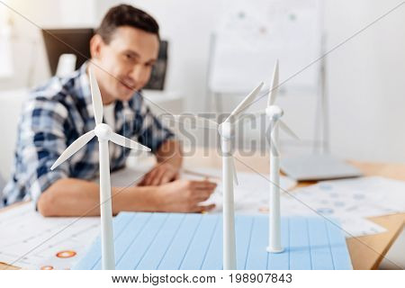 Work with diligence. Pleasant young man sitting at the table and drawing a sketch while thoroughly copying the details of wind turbine construction, being in the focus