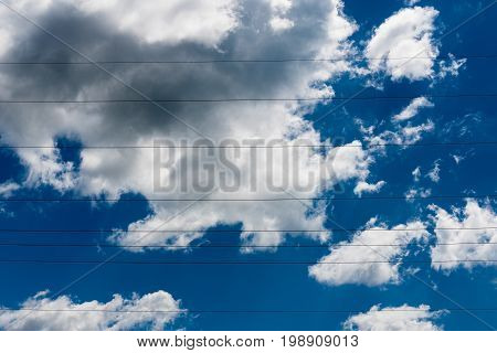 Blue skies with clouds and electrical cables across it