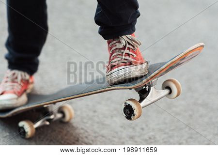 unrecognizable skateboarder with red sneakers. Streetwear, footwear and urban style of hipster who ride on back wheels of skate.